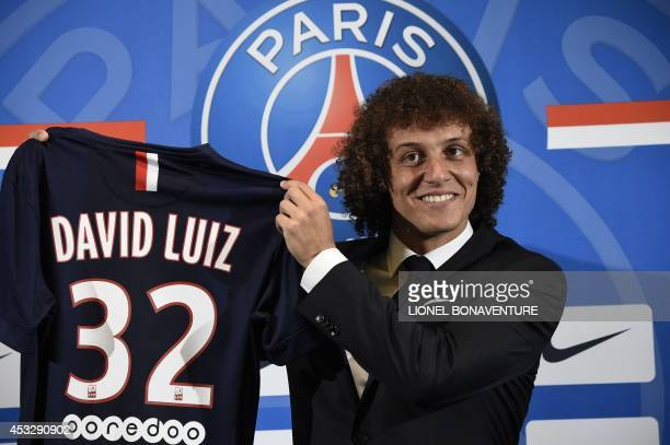 PSG newly recruited Brazilian defender David Luiz holds his new jersey during his official presentation on August 7 2014 in Paris Luiz signed in June...