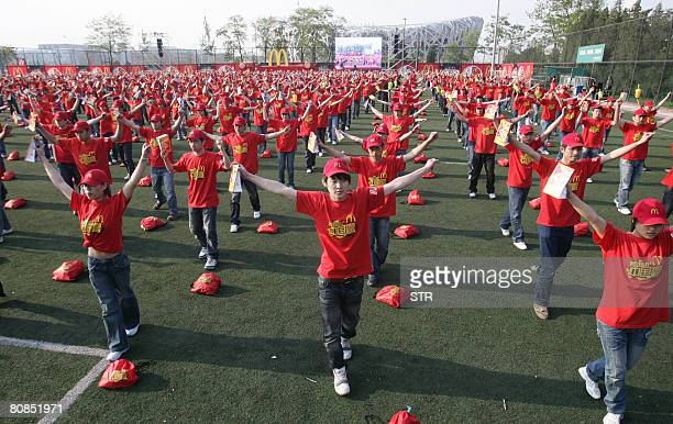 Newly recruited staff of US fastfood giant McDonald's for the 2008 Beijing Olympic Games work out during a ceremony at the Olympic Green in Beijing...