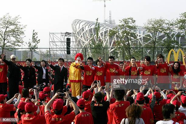 Newly recruited staff of US fastfood giant McDonald's for the 2008 Beijing Olympic Games gather for a ceremony at the Olympic Green in Beijing on...