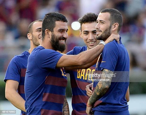 Newly signed midfielder Arda Turan of FC Barcelona hugs teammate Aleix Vidal as Munir El Haddadi and Sandro Ramirez look on during team warm up prior...