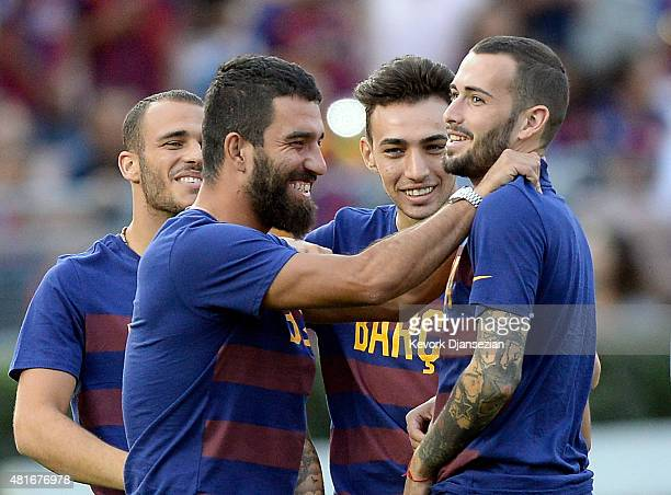 Newly signed midfielder Arda Turan of FC Barcelona hugs teammate Aleix Vidal as Munir El Haddadi and Sandro Ramirez look on during team warm up prior...