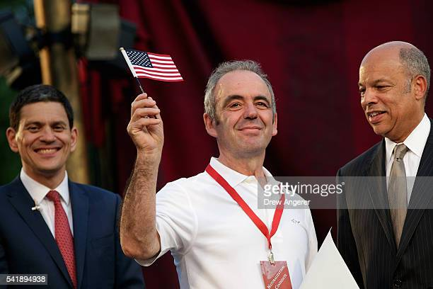 Newly sworn in American citizen Leke Kalaj from Albania waves his American flag after accepting her Certificate of Naturalization from Jeh Johnson...