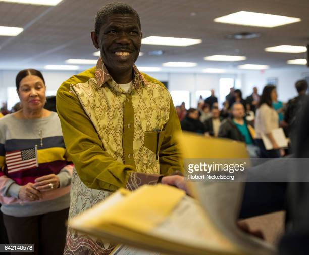 A newly sworn in US citizen center receives his Certificate of Naturalization from a US government employee right during a naturalization ceremony...