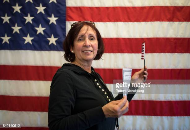 A newly sworn in US citizen originally from Venezuela stands for a picture holding her Certificate of Naturalization during a ceremony for new US...