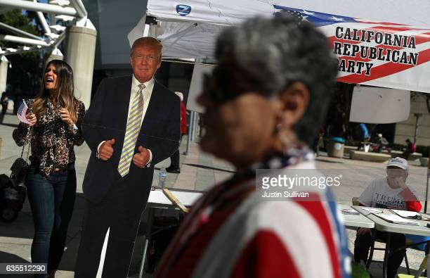 A newly sworn in US citizen takes a picture with a cardboard cutout of US President Donald Trump during a naturalization ceremony held by US...