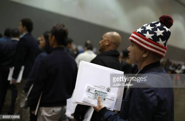 Newly sworn in US citizens wait in line to receive paperwork at the conclusion of a naturalization ceremony held by US Citizenship and Immigration...