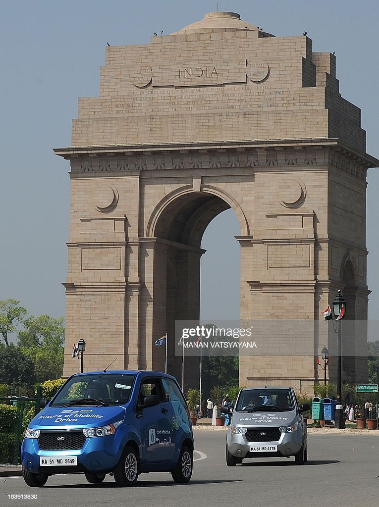 Newly unveiled Mahindra E20 electric cars drive past India Gate in New Delhi on March 18, 2013. Mahindra launched the new environment friendly E20 electric car powered by next generation Lithium-ion batteries and which can run up to 100 kms per charge. AFP PHOTO/ MANAN VATSYAYANA