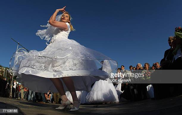 A newly wed bride dances at Michail's square in Kiev 29 September 2007 during a mass wedding where seventy couples took part AFP PHOTO/JOE KLAMAR