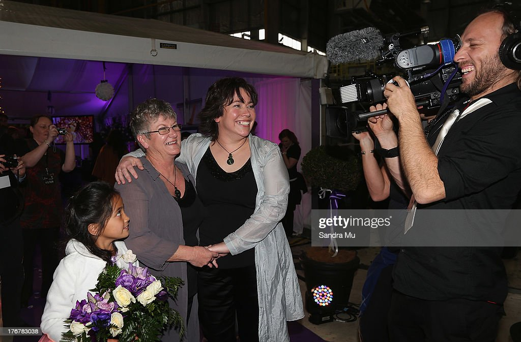 Newly wed couple Ally Wanikau (L) and Lynley Bendall share a moment with media during the reception inside the Air New Zealand hanger on August 19, 2013 in Auckland, New Zealand. New Zealand passed a bill to legalize same-sex marriage as of August 19, 2013. New Zealand is the first coutry in Oceania to leaglize same-sex marriage.