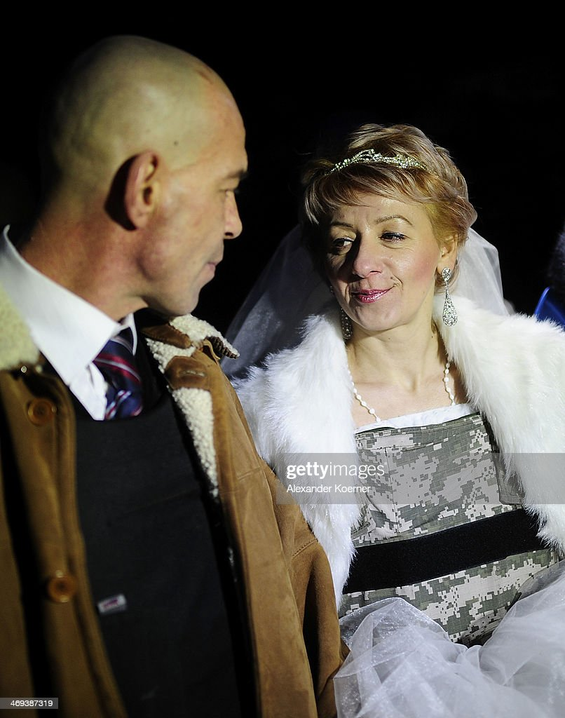 A newly wed couple is pictured in front a barricade on Grushevskogo Street on February 14, 2014, in Kiev, Ukraine. According to Opposition Officals, Berkut police forces could attack the barricades any moment; protesters have gathered inside and prepared fireworks and molotov-cocktails. Media and other people were removed from the barricades. Russian Foreign Minister Sergei Lavrov again issued a warning to the West against interfering in Ukraine's political crisis during today's joint press conference with German federal foreign Minister Walter Steinmeier, who is on a two-day visit to Russia. According to reports Ukrainian opposition leaders Vitaly Klitschko and Arseny Yatsenyuk are set to meet with German Chancellor Angela Merkel on February 18, 2014 in Germany.