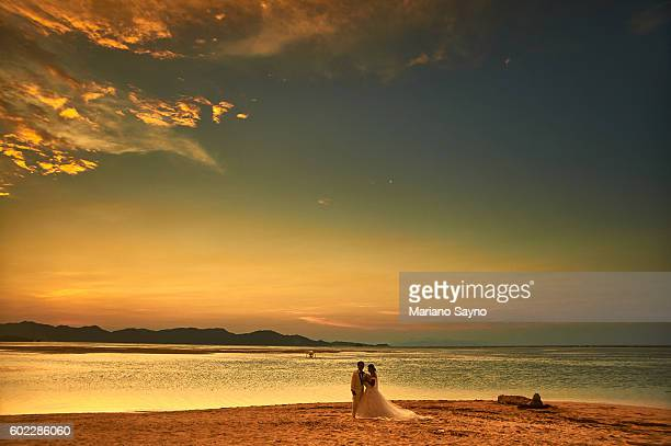 Newly Wed couple Standing At Shore during sunset
