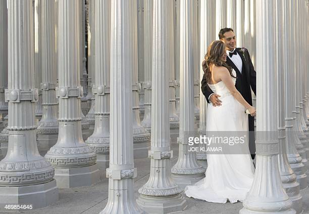 'MANDATORY MENTION OF THE ARTIST UPON PUBLICATION' A newly wedded couple pose for thier photographer under the columns of Urban Lights in front of...