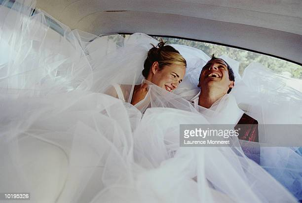 Newly weds laughing in back of car
