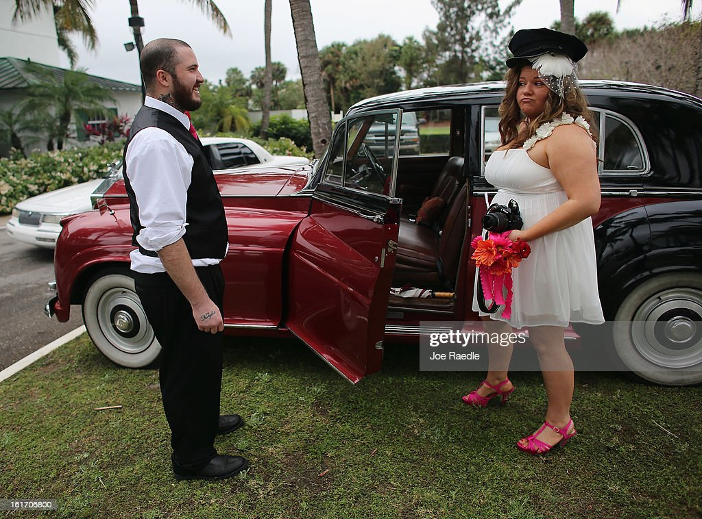 Newly weds Robert Homa and Ashley Homa ham it up near a Rolls-Royce vehicle after taking part in a group Valentine's day wedding at the National Croquet Center on February 14, 2013 in West Palm Beach, Florida. The group wedding ceremony is put on by the Palm Beach Country Clerk & Comptroller's office and approximately 40 couples to tied the knot.