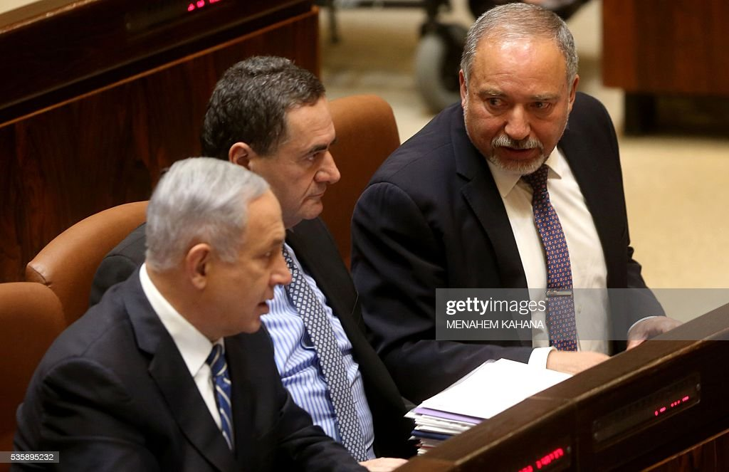 Newly-appointed Israeli Defence Minister Avigdor Lieberman (R), Minister of Transport Yisrael Katz (C) and Israeli Prime Minister Benjamin Netanyahu (L) attend a Knesset (Israeli parliament) session in which Lieberman was sworn in, on May 30, 2016, in Jerusalem. Lieberman was sworn in as Israel's new defence minister after winning support in the cabinet and in parliament, ending weeks of political intrigue and outrage. Netanyahu's cabinet voted to expand his coalition and appoint Lieberman, before the 120-seat Knesset approved him by a vote of 55-43. KAHANA