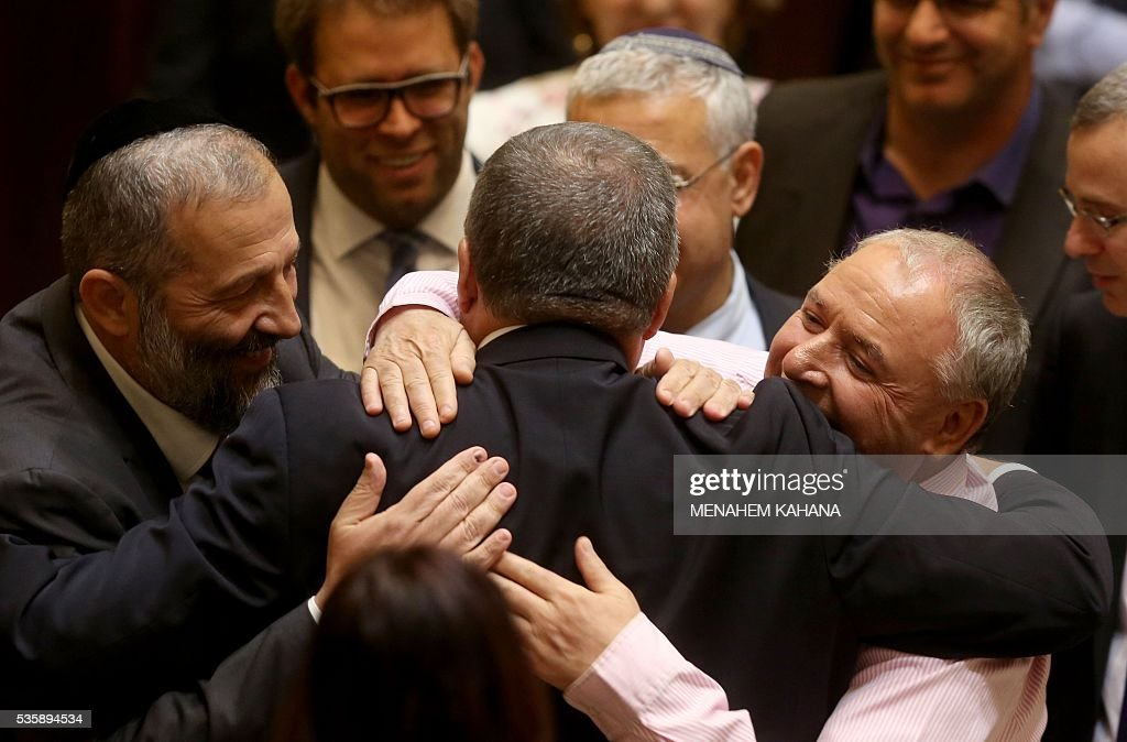 Newly-appointed Israeli Defence Minister Avigdor Lieberman (C), the head of hardline nationalist party Yisrael Beitenu, is congratulated by MPs after he was sworn in during a Knesset (Israeli parliament) session on May 30, 2016, in Jerusalem. The Israeli parliament approved Lieberman as the country's new defence minister hours after Prime Minister Benjamin Netanyahu's cabinet endorsed him. Lieberman, who has pledged harsh measures against Palestinian 'terrorists', was approved by 55 members of the 120-seat Knesset while 43 voted against, one abstained and the others were absent. KAHANA