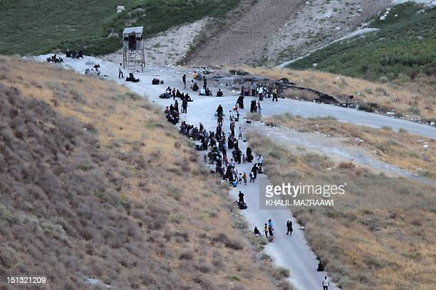 Newlyarrived Syrian refugees sit on the road after crossing the border from Syria into Jordan near the town of Ramtha on September 5 2012 Arab...