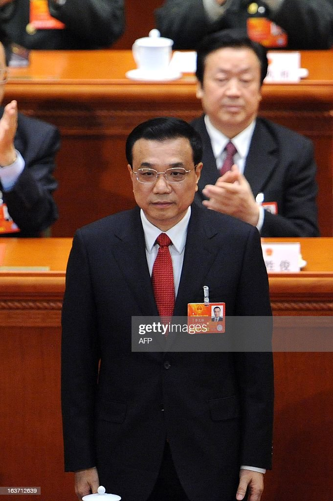 Newly-elected Chinese Premier Li Keqiang acknowledges the applause from delegates during the 12th National People's Congress (NPC) in the Great Hall of the People in Beijing on March 15, 2013. China's parliament installed bureaucrat Li Keqiang as premier on March 15, putting him in charge of running the world's second-largest economy in a final step of a landmark power transition.