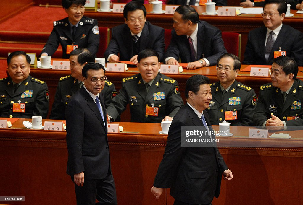 Newly-elected Chinese Premier Li Keqiang (L) and President Xi Jinping (R) walk past military delegates including new Defense Minister Chang Wanquan (R) during the election of the new vice premiers, foreign and defense ministers of China during the 12th National People's Congress (NPC) in the Great Hall of the People in Beijing on March 16, 2013. China's parliament named Xi Jinping as president on March 15 four months after he took charge of the Communist Party with pledges of reform that have raised hopes but so far yielded little change. AFP PHOTO / Mark RALSTON