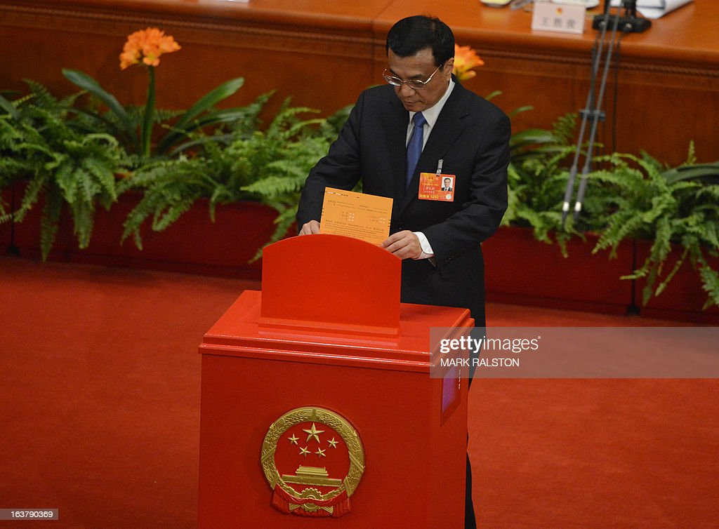 Newly-elected Chinese Premier Li Keqiang votes during the election of the new vice premiers, foreign and defense ministers of China during the 12th National People's Congress (NPC) in the Great Hall of the People in Beijing on March 16, 2013. China's parliament on March 16 approved Wang Yi, a former ambassador to Japan and currently in charge of Taiwan affairs, to be the country's new foreign minister. AFP PHOTO / Mark RALSTON