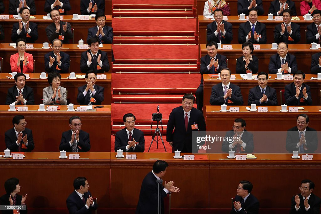 Newly-elected Chinese President Xi Jinping (3rd R) bows after he was also elected as Chairman of the Central Military Commission, with former President Hu Jintao (3rd L), Vice Premier Li Keqiang (2nd R) clapping hands during the fourth plenary meeting of the National People's Congress (NPC) at the Great Hall of the People on March 14, 2013 in Beijing, China. Xi Jinping, general secretary of the Communist Party of China Central Committee, was elected President of the People's Republic of China and Chairman of the Central Military Commission on Thursday.
