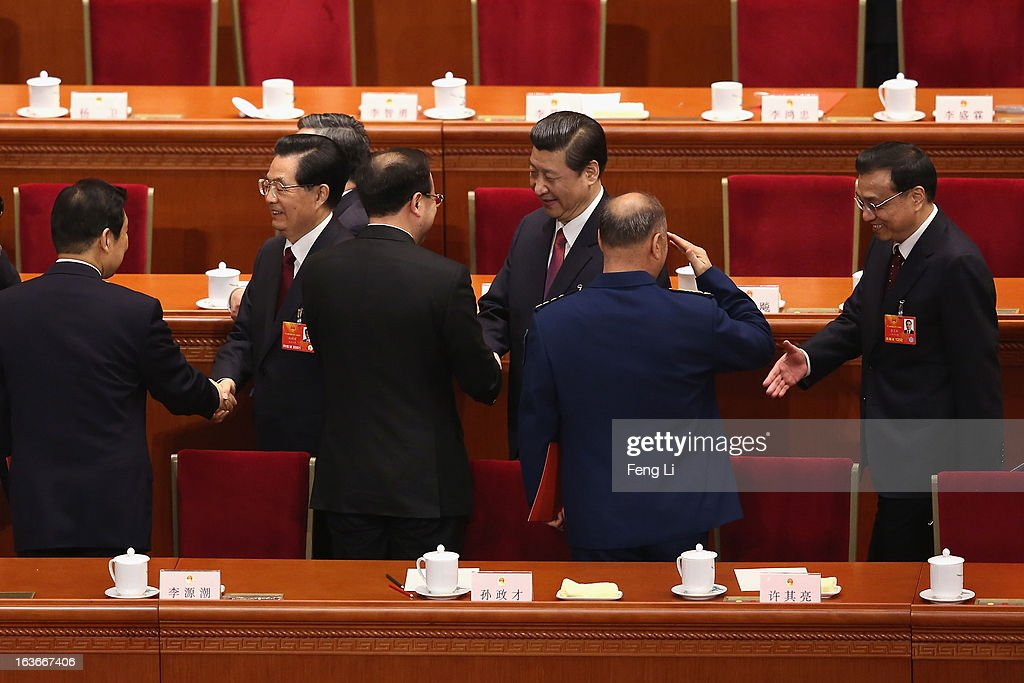 Newly-elected Chinese President Xi Jinping (C) together with former President Hu Jintao (L) and incoming Premier Li Keqiang (R) greet delegates as they leave after the fourth plenary meeting of the National People's Congress (NPC) at the Great Hall of the People on March 14, 2013 in Beijing, China. Xi Jinping, general secretary of the Communist Party of China Central Committee, was elected President of the People's Republic of China and Chairman of the Central Military Commission on Thursday.