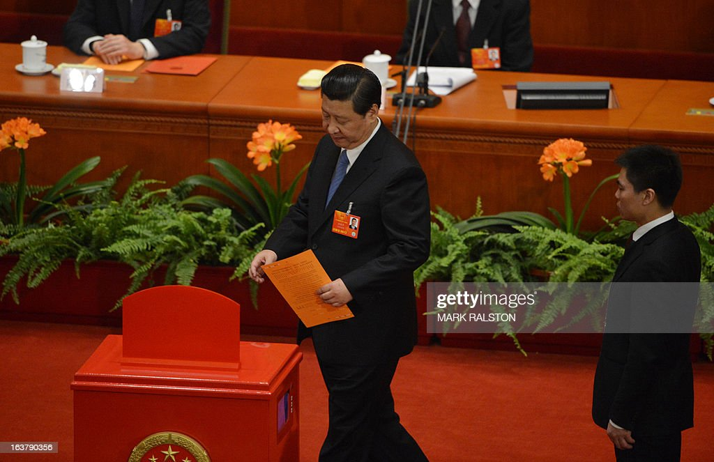 Newly-elected Chinese President Xi Jinping (C) votes during the election of the new vice premiers, foreign and defense ministers of China during the 12th National People's Congress (NPC) in the Great Hall of the People in Beijing on March 16, 2013. China's parliament named Xi Jinping as president on March 15 four months after he took charge of the Communist Party with pledges of reform that have raised hopes but so far yielded little change. AFP PHOTO / Mark RALSTON