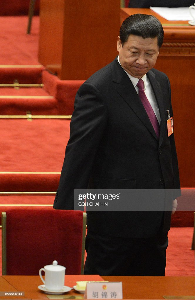 Newly-elected Chinese President Xi Jinping walks past former Chinese President Hu Jintao's seat at the closing session of the National People's Congress (NPC) at the Great Hall of the People in Beijing on March 17, 2013. China's new Premier Li Keqiang steps into the media spotlight on March 17 for a rare press conference, as the annual meeting of the country's rubber-stamp parliament closes. AFP PHOTO/GOH CHAI HIN