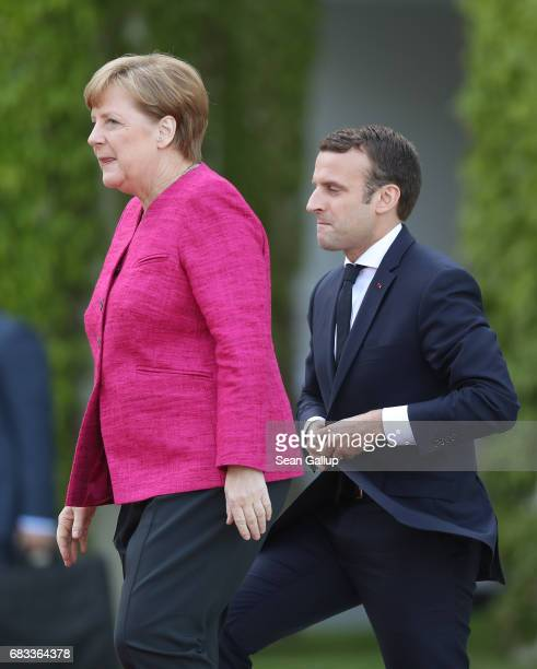 Newlyelected French President Emmanuel Macron and German Chancellor Angela Merkel prepare to review a guard of honour upon Macron's arrival at the...