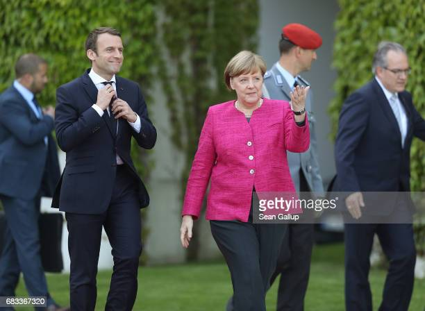 Newlyelected French President Emmanuel Macron and German Chancellor Angela Merkel walk to review a guard of honour upon Macron's arrival at the...