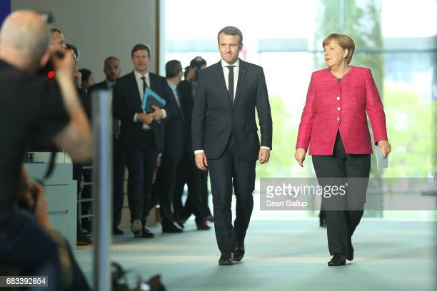 Newlyelected French President Emmanuel Macron and German Chancellor Angela Merkel arrive to speak to the media following talks at the Chancellery on...
