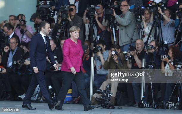 Newlyelected French President Emmanuel Macron and German Chancellor Angela Merkel walk past photographers upon Macron's arrival at the Chancellery on...