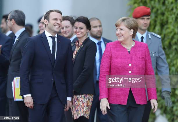 Newlyelected French President Emmanuel Macron and German Chancellor Angela Merkel share a laugh upon Macron's arrival at the Chancellery on May 15...