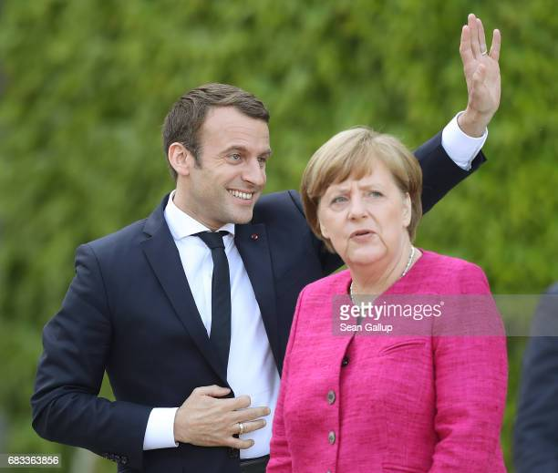 Newlyelected French President Emmanuel Macron waves to cheering onlookers as German Chancellor Angela Merkel looks on upon Macron's arrival at the...