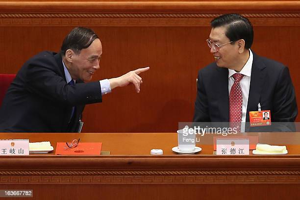 Newlyelected NPC Chairman Zhang Dejiang talks with Chinese Vice President Wang Qishan during the fourth plenary meeting of the National People's...
