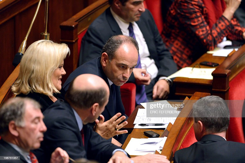 Newly-elected president of the right-wing UMP opposition party, Jean-Francois Cope talks with a MP during the weekly session of questions at the National Assembly on November 20, 2012 in Paris.