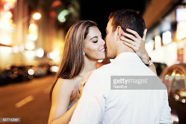 Newly-engaged couple share romantic kiss in nighttime street