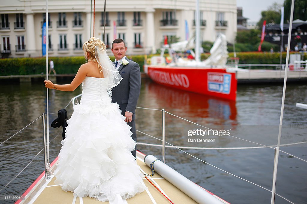 A newly-married couple pose on the Team GB entry of the 12 race yachts competing in The Clipper 2013-14 Round The World Yacht Race after it moored in St Katherine's Dock, east London on August 23, 2013. The 40,000 mile, 8-leg course begins on September 1 and will visit six continents, taking eleven months to complete.