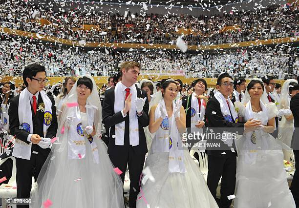 Newlymarried couples applaud at the end of the mass wedding organised by the Unification Church and held in its headquarters in Gapyeong east of...