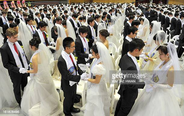 Newlymarried couples hold hands to pray during a mass wedding organised by the Unification Church and held in the church's headquarters in Gapyeong...