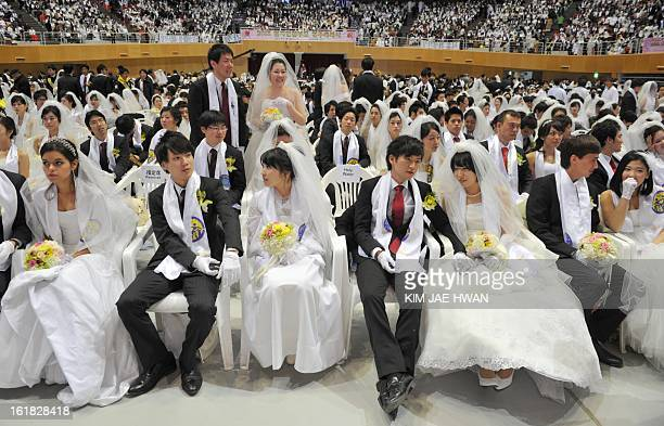 Newlymarried couples sit down at the Unification Church's mass wedding held at the church's headquarters in Gapyeong east of Seoul on February 17...