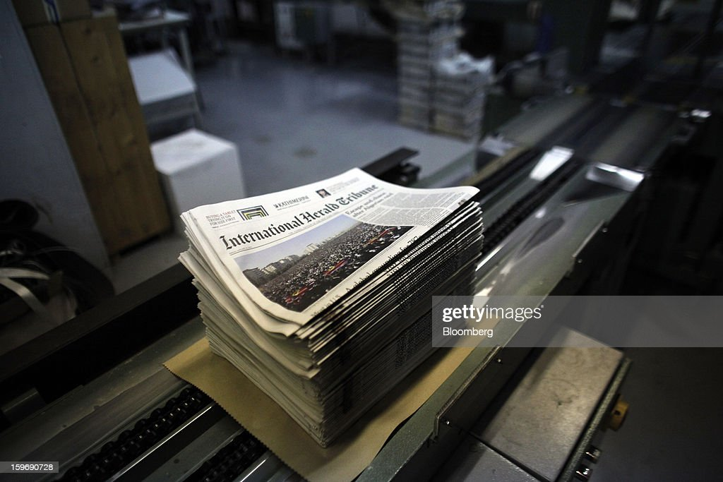 Newly-printed editions of the International Herald Tribune newspaper sit stacked for packaging on a conveyor belt at the Kathimerini printing plant in Paiania, Greece, on Thursday, Jan. 17, 2013. An anarchist group claimed responsibility for a series of attacks early on Jan. 11 when unidentified perpetrators threw makeshift bombs made from propane gas canisters into the homes of five Greek journalists working for national media saying it was to protest coverage of the country's financial crisis seen as sympathetic to the government. Photographer: Kostas Tsironis/Bloomberg via Getty Images