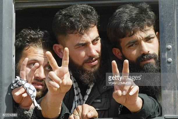 Newlyreleased prisoners flash the victory sigen 21 February 2005 as a busload of Palestinians released from Israeli custody arrives at a checkpoint...