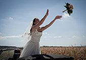 Newlywed bride tossing bouquet from car