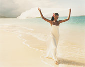 Newlywed Bride Walks at Waters Edge Holding a Veil Above her Head