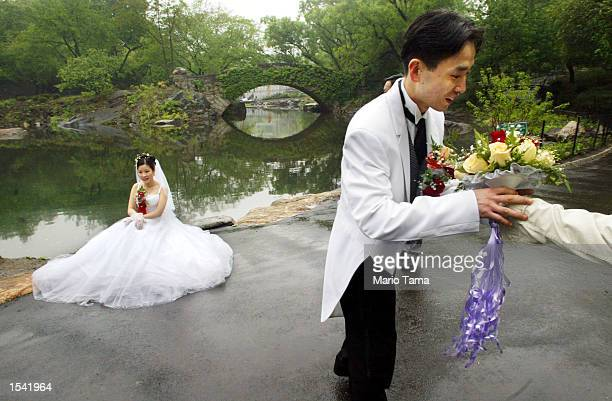Newlywed Chenjean and Tina Moeing brave a drizzling rain as they prepare to pose for a photographer in Central Park May 13 2002 in New York City A...