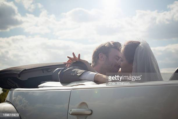 Newlywed couple about to kiss in a convertible