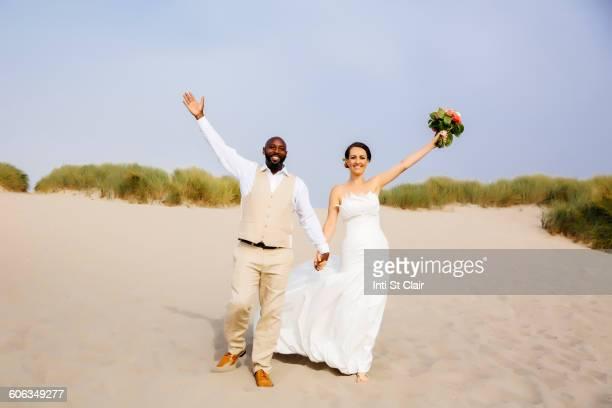 Newlywed couple cheering on beach