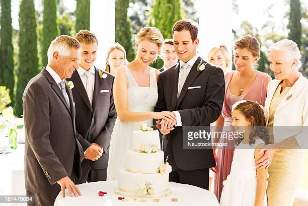 Newlywed Couple Cutting Wedding Cake During Reception