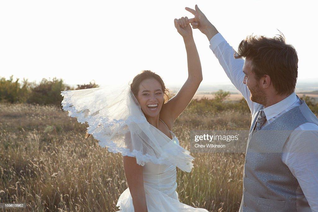 Newlywed couple dancing outdoors